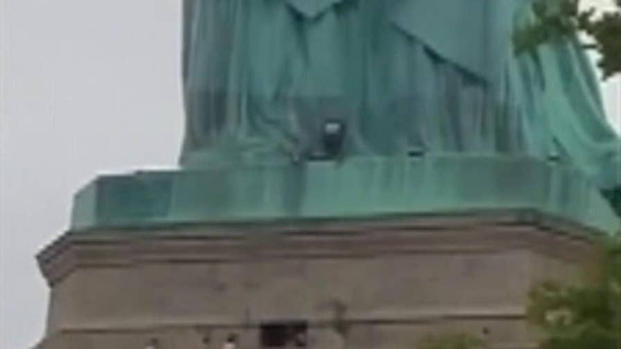 The protestor climbed from the pedestal area to the base of the statue, forcing an evacuation.