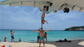 Performers Oleg Kolisnichenko and Yulia Nos appear to be just feet away from a low-flying aircraft on Maho Beach.