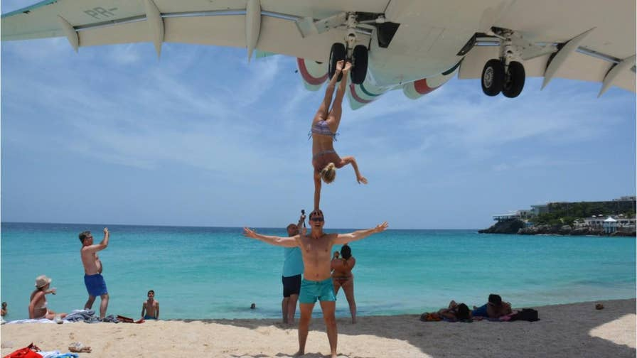 A couple is in hot water after doing an acrobatic stunt several feet below a descending airplane on Maho Beach in Saint Martin.