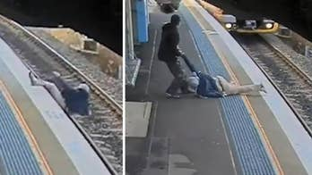 Raw video: Security footage captures man falling onto tracks fellow commuter pulling him from the path of an oncoming train as it grinds to a halt at Sydney station.
