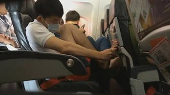 An AirAsia passenger was caught on camera picking his toe nails much to the chagrin of fellow passengers.