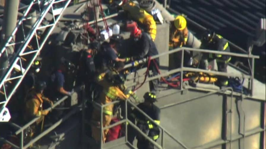 Firefighters in California work to rescue a man who is stuck in a large hopper of dry cement.