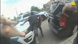 Footage from body cameras and other surveillance video appeared to show that a black man who was shot and killed by a Chicago police officer was armed with a gun and reached toward it as officers confronted him, officials said Sunday.