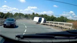 This video shows the see-it-to-believe-it moment when a van driver dices with death by grinding along the edge of a road bridge.