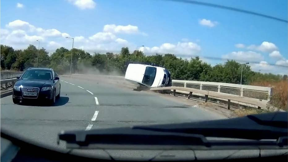 Out of control van grinds road barrier like a skateboarder