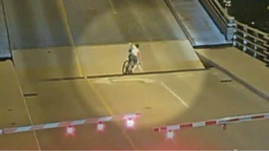 Surveillance video shows bystanders come to cyclist's rescue after the woman rode through warning gates and fell into gap.