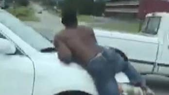 Shirtless man captured on video hanging onto moving car