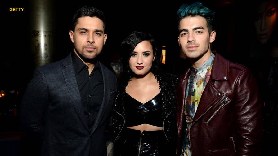 Demi Lovato's ex-boyfriends Wilmer Valderrama and Joe Jonas are reportedly reacting to the singer's apparent overdose on Tuesday after news broke that she is reportedly 'awake' and in 'stable' condition.