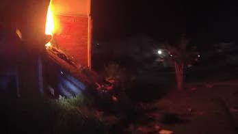Surveillance video captures the moment a man violently crashes a stolen Mercedes into an apartment building before it catches on fire. The incident left one man critically injured.