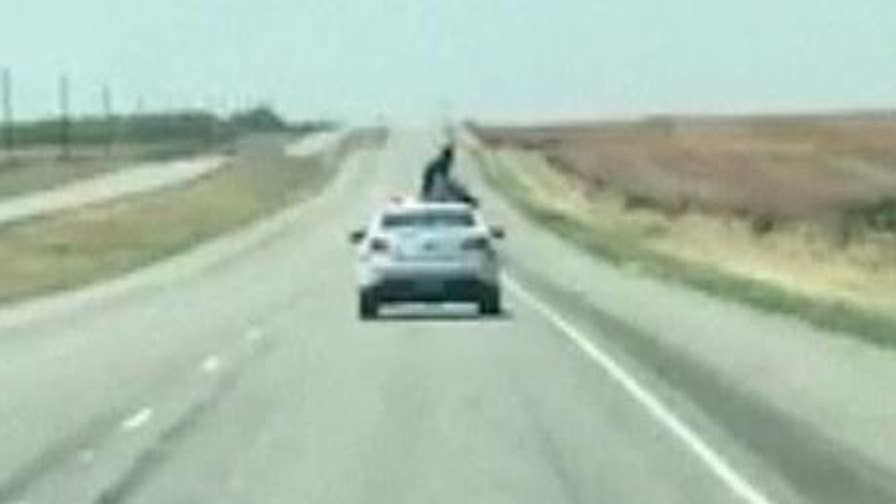 Raw video: A man being transported to jail kicked out a back window of a patrol car and climbed on top of the roof as it traveled down the highway.