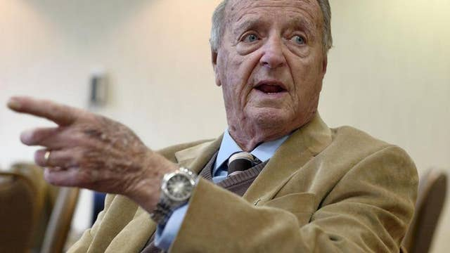 Bobby Bowden stands with kneeling football coach
