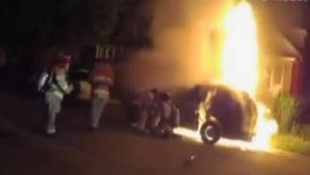 Body cam shows dramatic rescue of man trapped in burning minivan in Wisconsin.