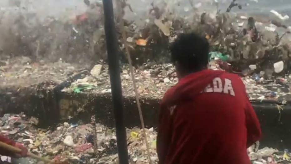 Volunteers struggle to clean garbage washing ashore
