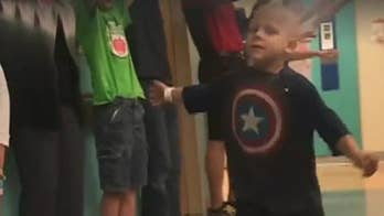 4-year-old is cheered on marching down the hallway after he finishes his last round of chemo.