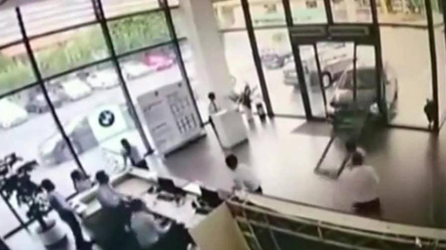 A woman in China accidentally returned her BMW X1 SUV test drive by crashing through the dealership's front doors.