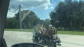 Florida motorcyclist seen leaning back, using feet to steer vehicle on interstate