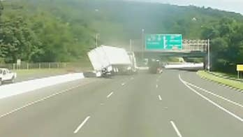 Dashcam footage shows a tractor trailer tipping over after aggressively changing lanes.