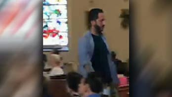 Man shouts and leaves during priest's sermon.
