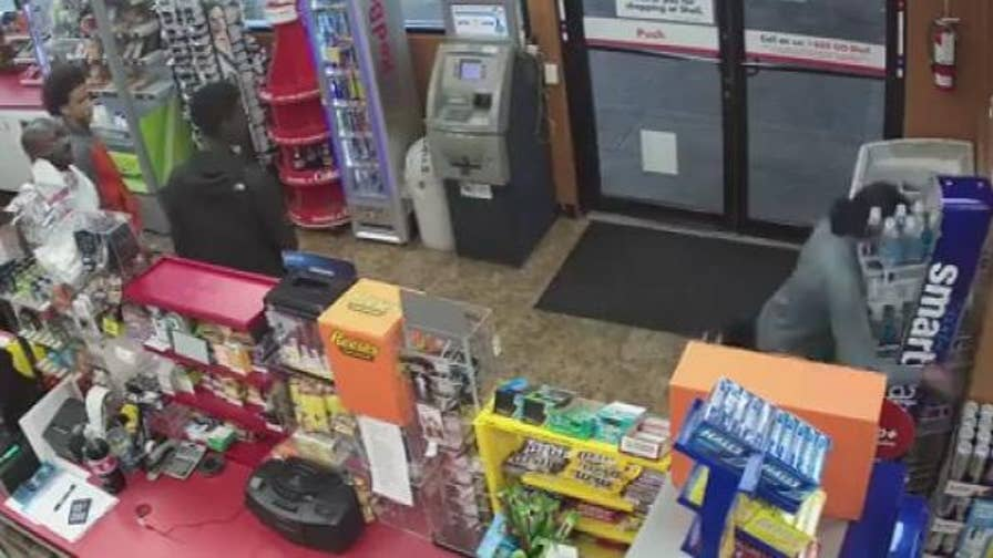 Raw Video: Three young men rob a gas station convenience store as the store clerk suffers a medical emergency and falls into a display stand.