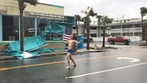 Video: Lane Pittman shows patriotism, holds U.S. flag against hurricane winds.