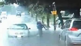 Raw video: Police Specialist Mathew Hernon assisted a motorist when her car became disabled in flood waters.
