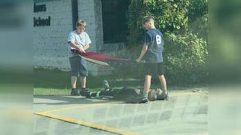 Boy lays down to keep flag from hitting the ground