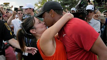After Tiger Woods sank a putt to seal his first PGA Tour victory in five years, his new mystery girlfriend stunned the crowd by wrapped her arms around him and giving him a victory kiss.