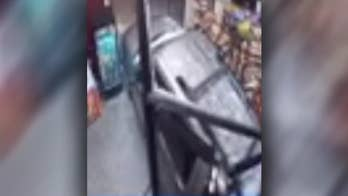 Surveillance video shows Michigan woman allegedly reversing car into store