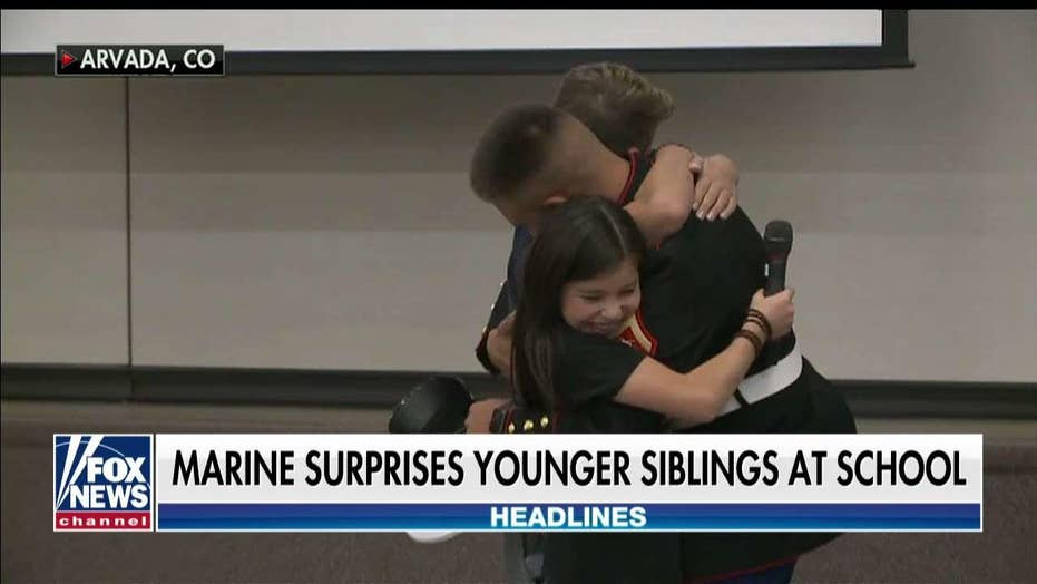 Marine surprises younger siblings at Veterans Day Assembly.