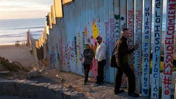 Arrival of migrant caravan renews focus on border wall