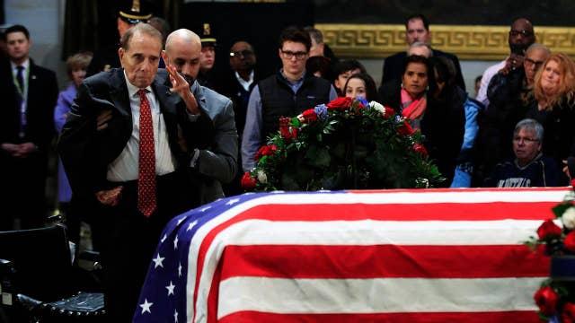 Fellow war hero Bob Dole honors George H.W. Bush