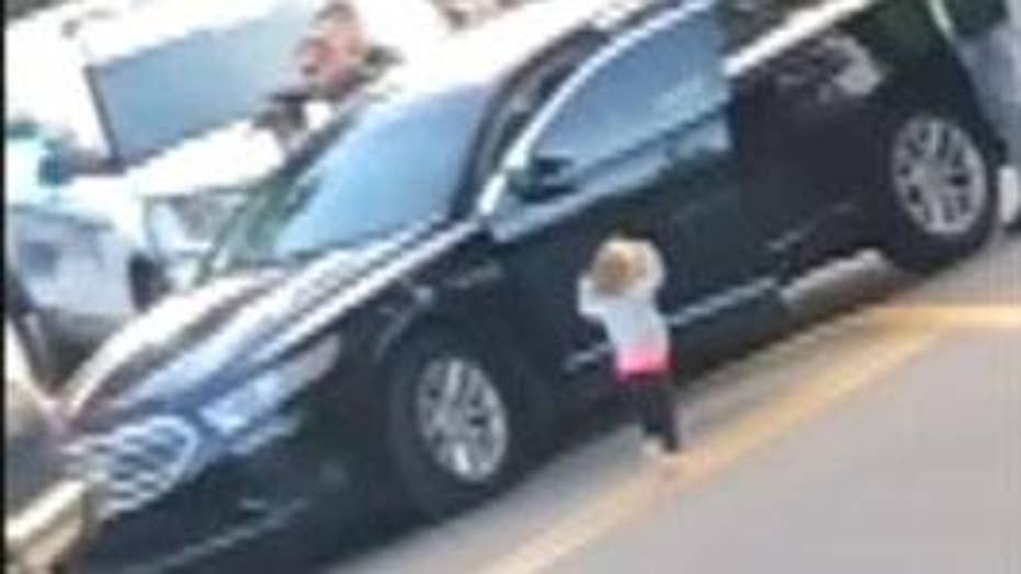 Toddler exits vehicle with hands up following her parents