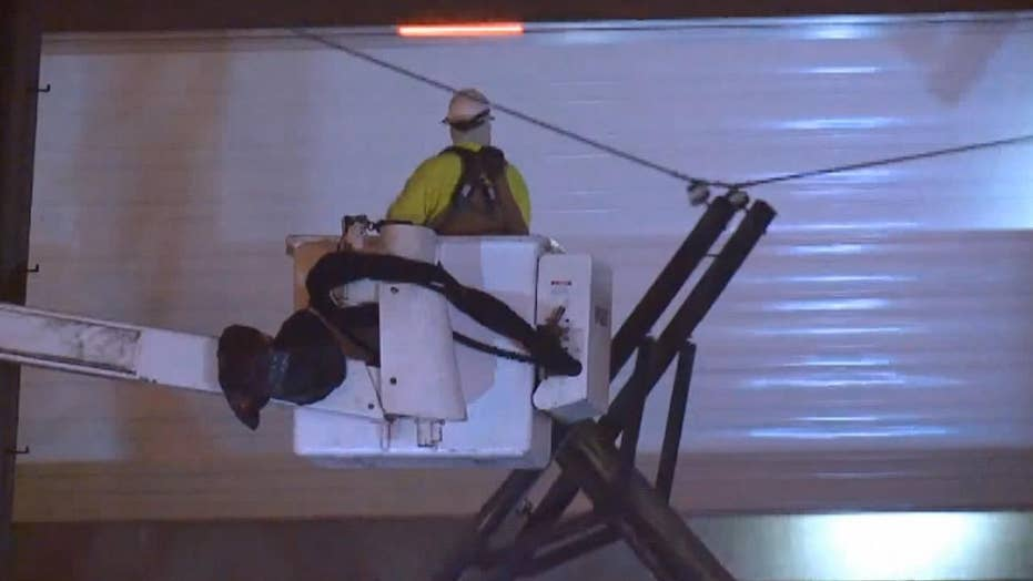 Utility worker on a lift jumps as semi pulls live wire from burning pole