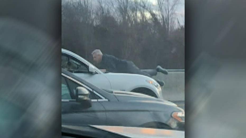Raw video: Man holds on to hood of speeding car