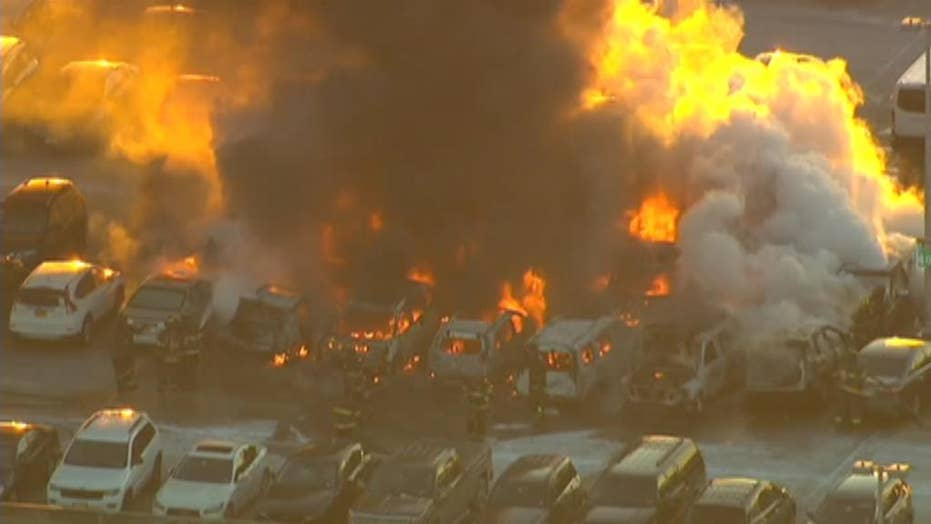 Firefighters worked to put out a raging fire at a Newark Airport parking garage; no injuries reported