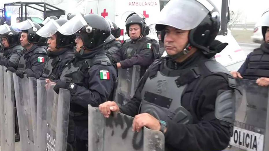 Mexican police in riot gear line up at US border as migrant caravan arrives