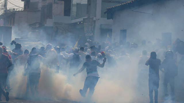Police and protestors clash in Venezuela as citizens attempt to push foreign aid across the closed border