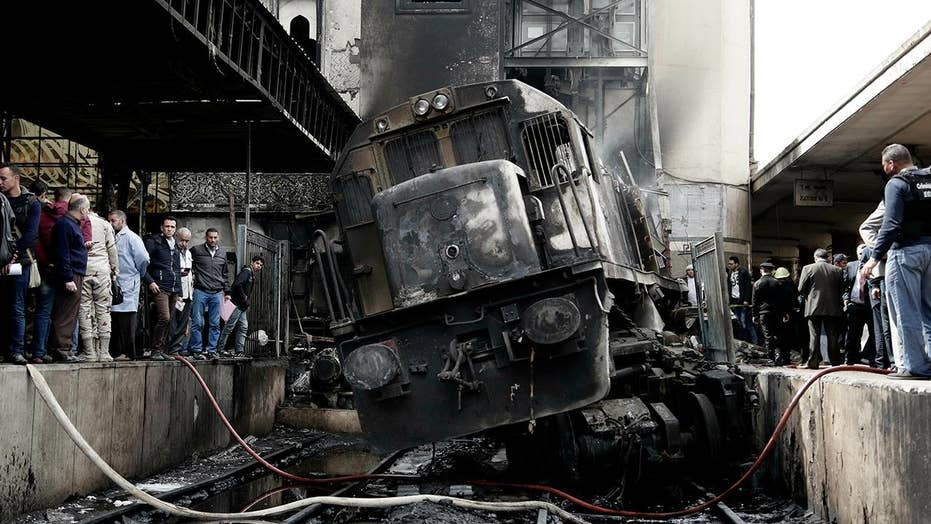 Dozens killed in Cairo station after train slams into barrier causing an explosion that triggered a fire