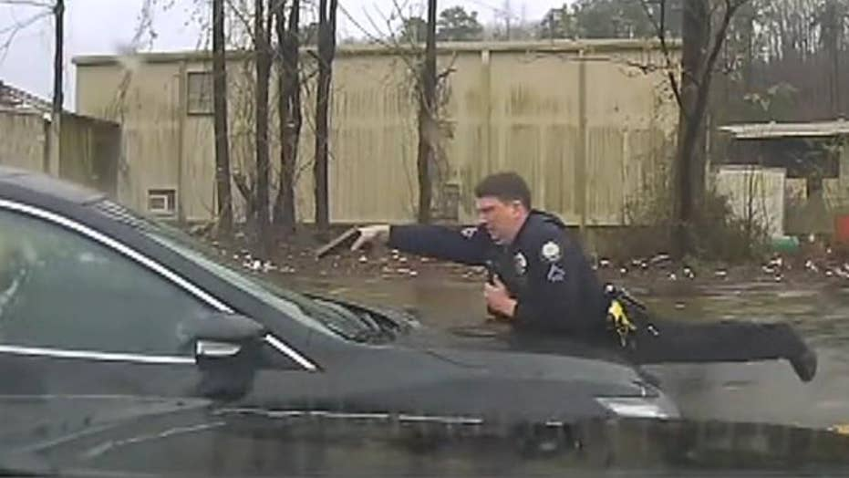 Arkansas police officer on hood of car fires at driver through windshield 15 times