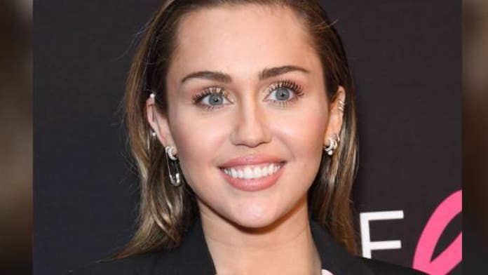 Miley Cyrus shows off her abs in skimpy black bikini