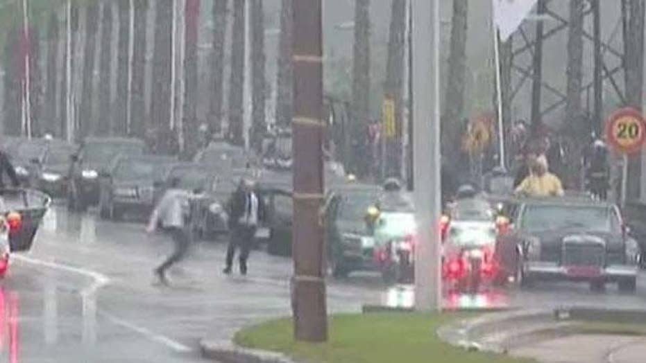 Man runs toward the motorcade of the king of Morocco and Pope Francis