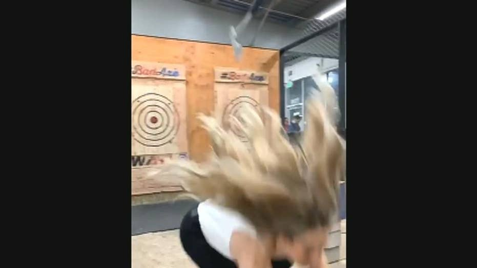 Woman at indoor entertainment center narrowly dodges ax playing popular game