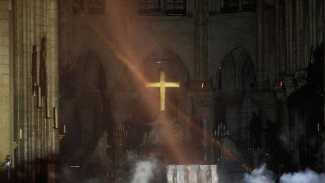 Notre Dame's golden altar cross seen glowing among the ashes as images emerge from inside show fire-ravaged cathedral