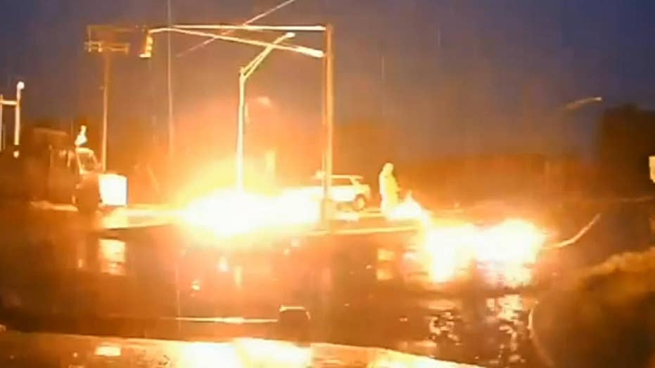 Utility worker narrowly avoids injury after damaged wires fall to ground and erupt into fireball