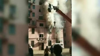 Crane operator rescues 14 people from burning building in China