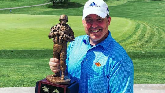 Ed Henry receives the Folds of Honor trophy during a charity golf tournament