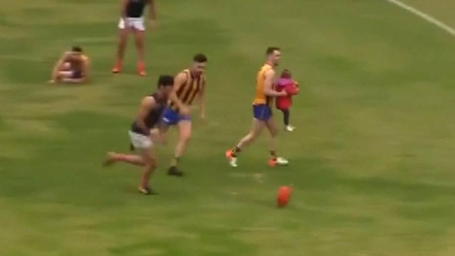 Toddler who ran onto field during game gets carried away by Australian rules football player