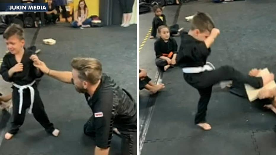 Karate class cheers on student having trouble breaking board