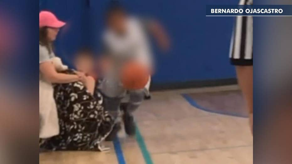 Parent sitting courtside appears to stick leg out as youth basketball player dribbles past