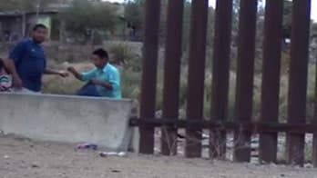 Footage of porous US-Mexico border purportedly shows armed coyote smuggling dozens with ease